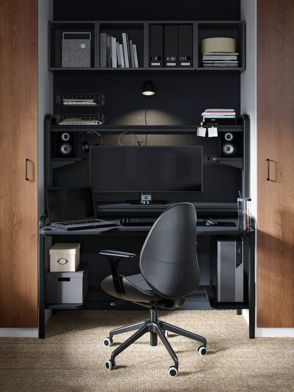 A black swivel chair in front of a black desk with storage, a screen on the desk and diverse items on the shelves.