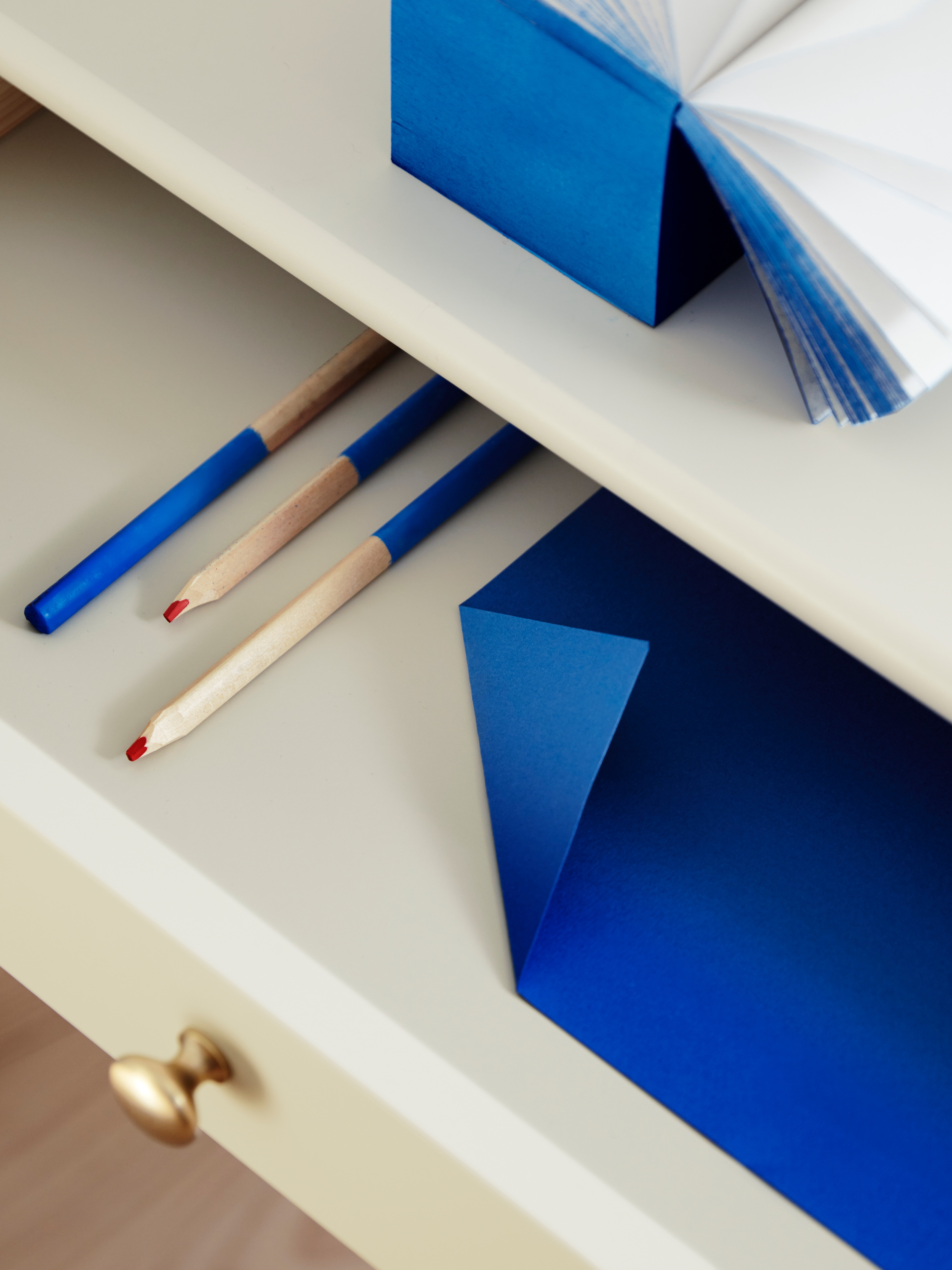 A close-up of a light beige LOMMARP desk with its solid pine drawer that has a gold knob open to show blue pencils and paper.