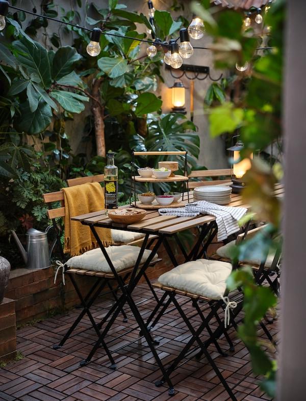 Un tavolo da giardino TARNÖ si trova in un cortile, decorato con cuscini e luci fatate. Luci solari SOLVINDEN appese a un balcone.