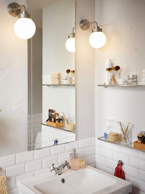 Une salle de bain de style traditionnel avec du carrelage blanc, deux lampes murales FRIHULT de part et d'autre d'un miroir mural.