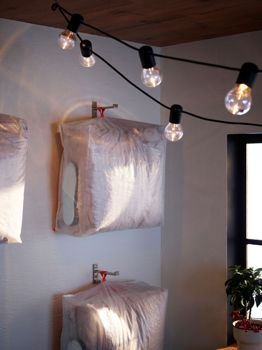 Arranged and hung on wall hooks, three PÄRKLA transparent storage cases hold bedding and night-time accessories for guests.
