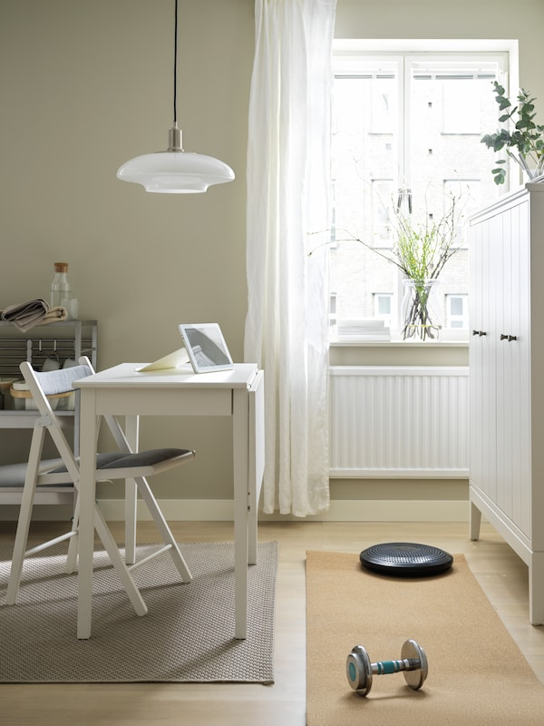 A yoga mat and weights placed between a TERJE chair and a white drop-leaf table combo, and a white IDANÄS cabinet.
