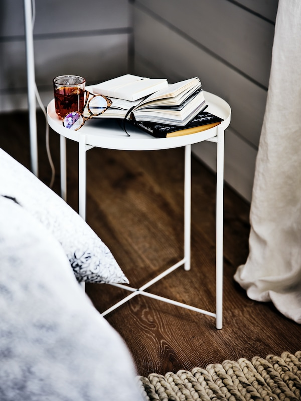 A white GLADOM coffee table in the corner of a room beside a bed, with some books, a pair of glasses and a drink on it.