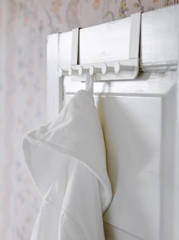 Un cuier ENUDDEN alb pentru ușă pe o ușă albă în stil tradițional, un halat de baie este agățat de unul dintre cârlige.