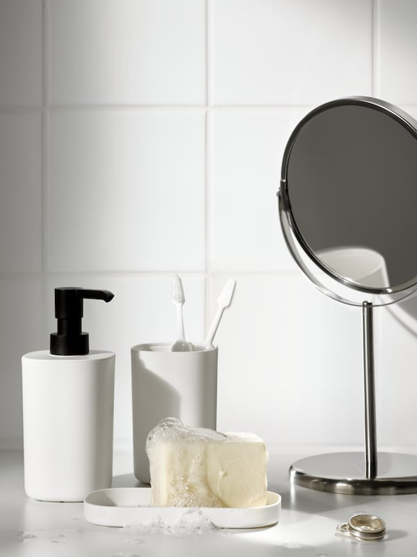 The white soap dispenser, tray and toothbrush holder of the STORAVAN bathroom set beside a mirror.