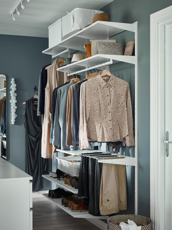 O zonă de dressing cu sistem de depozitare deschis alb, bluze și rochii atârnate pe șine și pantofi pe polițe deschise.
