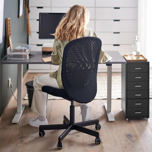 Eine Person sitzt auf einem schwarzen FLINTAN Drehstuhl an einem grauen RODULF Sitz-/Stehschreibtisch mit einem Computer und einem Schubladenelement.