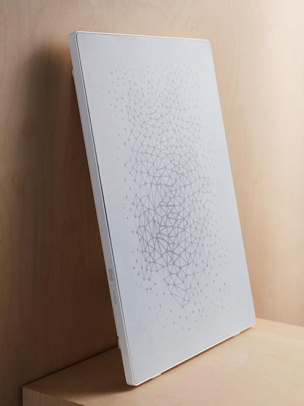 En vit SYMFONISK tavelram står lutad mot en vägg som en installation.