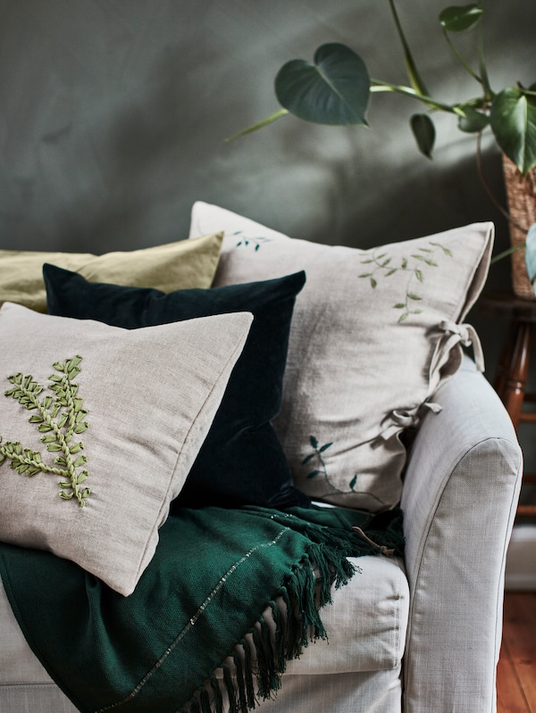One green and three beige cushions decorated with unique leaf embroideries on a light grey sofa with a dark green throw.