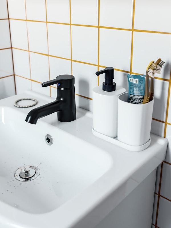 Satu sink mangkuk berwarna putih, paip berwarna hitam dan bekas berus gigi berwarna putih, pendispens sabun dan dulang.