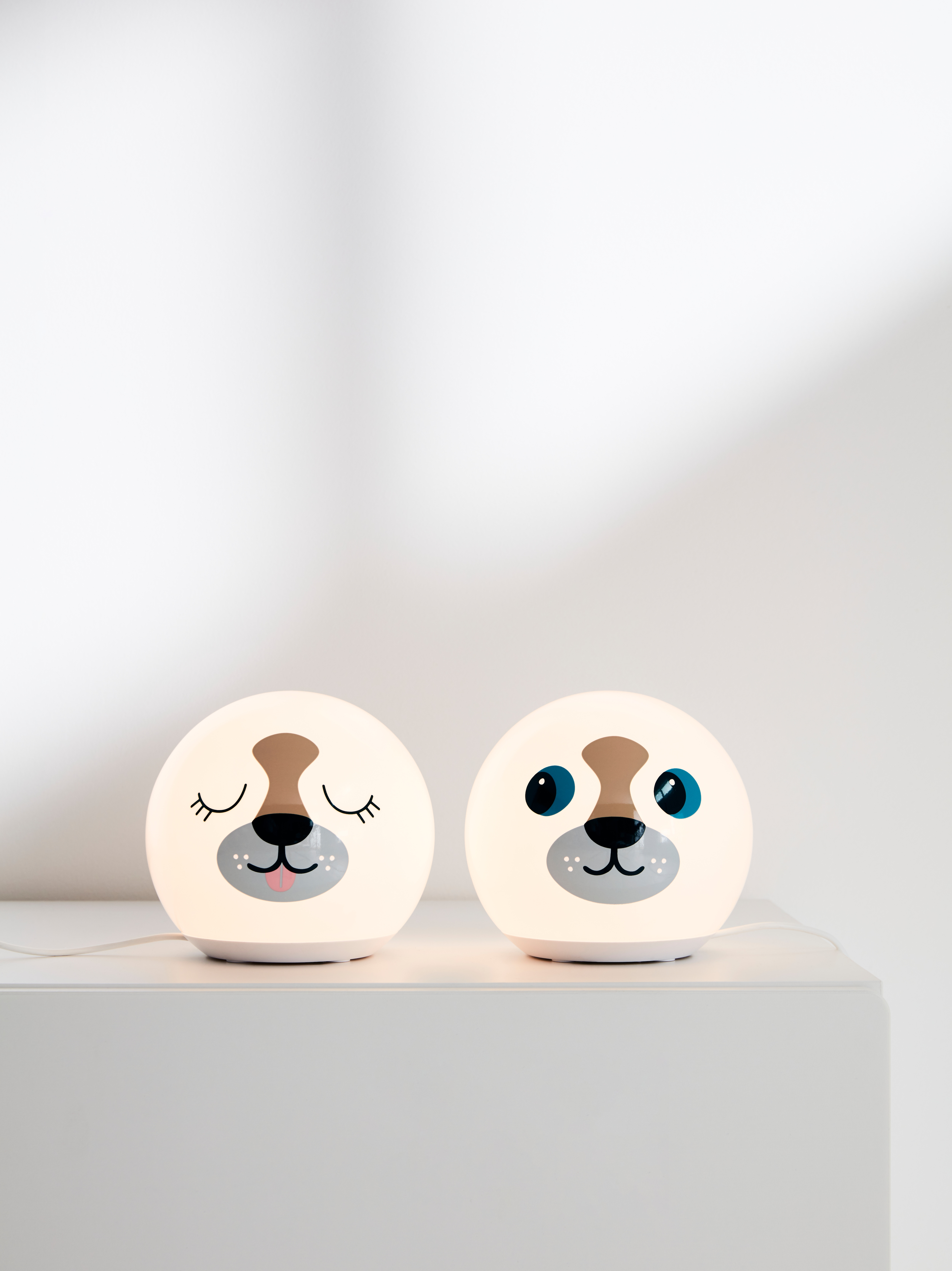 Two lit ÄNGARNA LED table lamps that look like dogs, one with eyes open and one with eyes closed, on a grey display plinth.