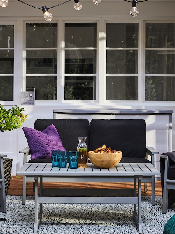 A grey table outside, on a rug holding a bowl, a carafe and some glasses, in front of a sofa and a purple cushion.