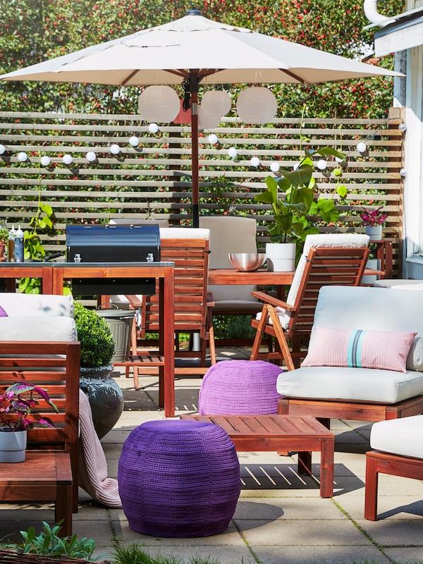 Un espace extérieur, doté de tables extérieures, de chaises et d'un parasol, avec des coussins, des poufs et des lampes.