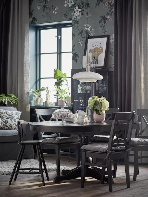 Egy tradicionális stílusú étkező kerek, fekete meghosszabbítható INGATORP asztallal és négy fekete-barna INGOLF székkel, illetve egy gyerekszékkel.