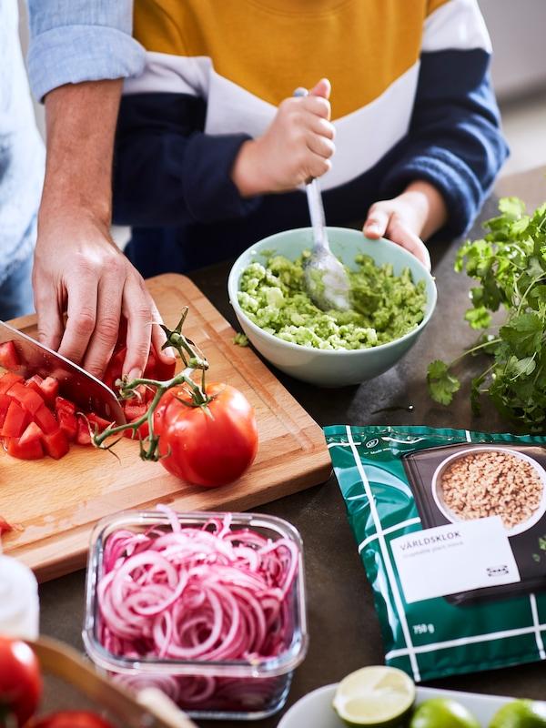 """Paczka z roślinnym """"mięsem"""" mielonym VÄRLDSKLOK leżąca na blacie obok pojemnika z marynowaną czerwoną cebulą. Obok mężczyzna kroi pomidory, a dziecko miesza guacamole."""