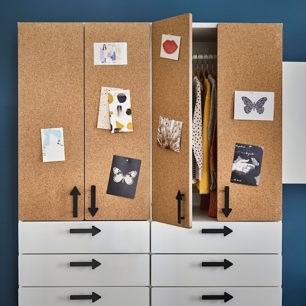 Two SMÅSTAD wardrobes with white drawers, cork doors and arrow-shaped handles stand in a kid's room. One has an open door.
