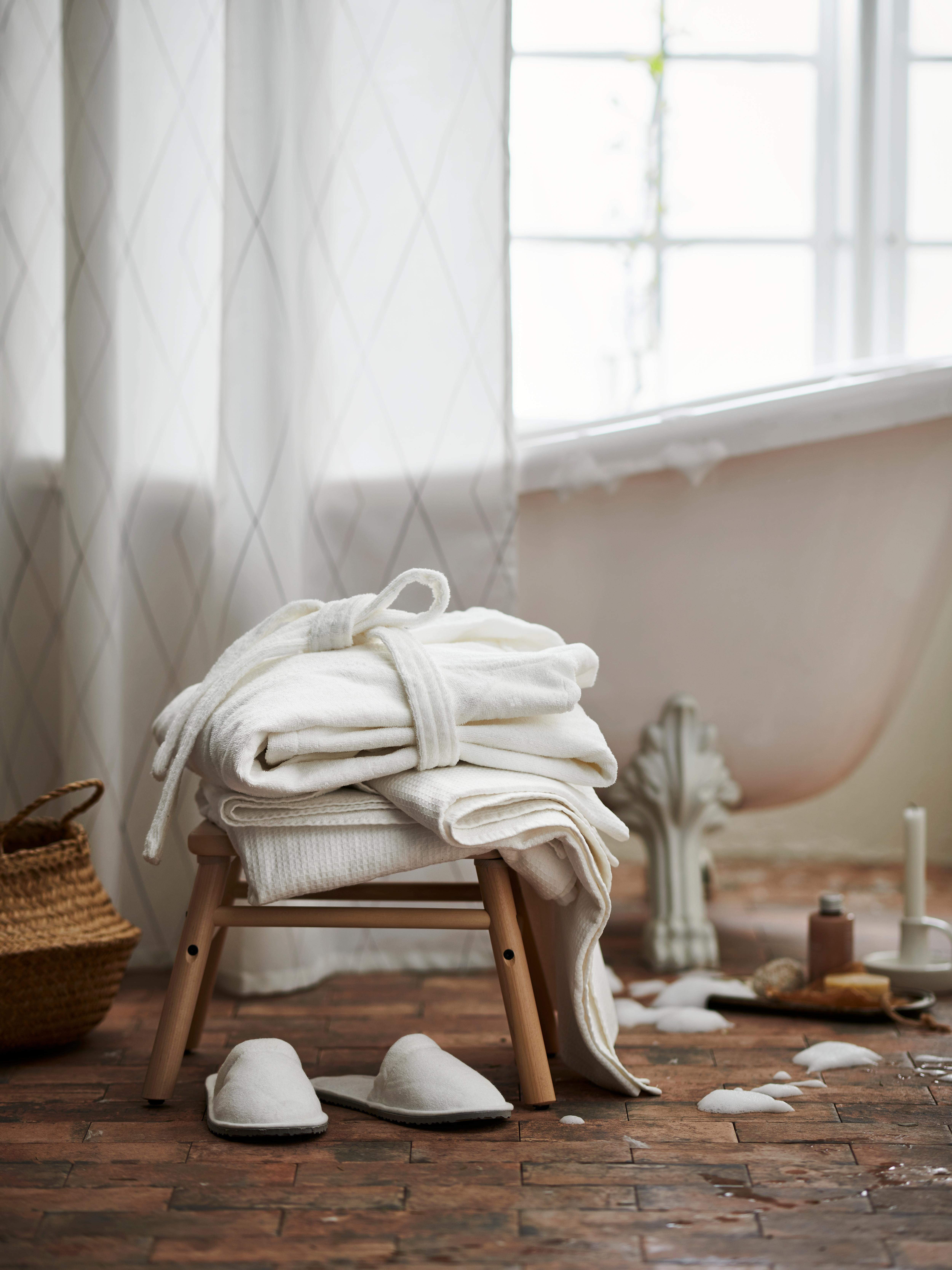 Valkoinen kylpytakki ja pyyhe puisella jakkaralla lattialla olevien valkoisten tohveleiden ja kylpyvaahtoroiskeiden vieressä. Taustalla näkyy osittain suihkuverhon suojassa oleva kylpyamme.