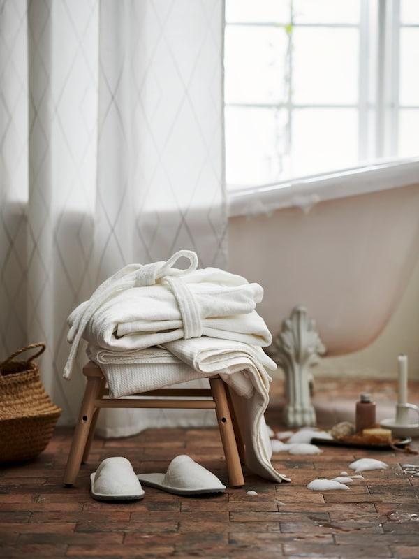Kylpytakki ja pyyhkeitä jakkaralla kylpyhuoneessa