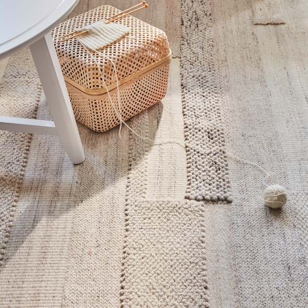 A beige rug with the edge of a white wooden chair and a woven basket.