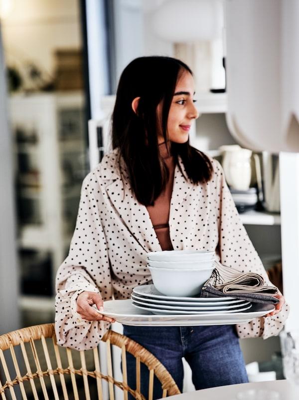 Une jeune femme tient un plateau sur lequel se trouvent des assiettes et des bols, à côté d'une table et d'un fauteuil en rotin NILSOVE.