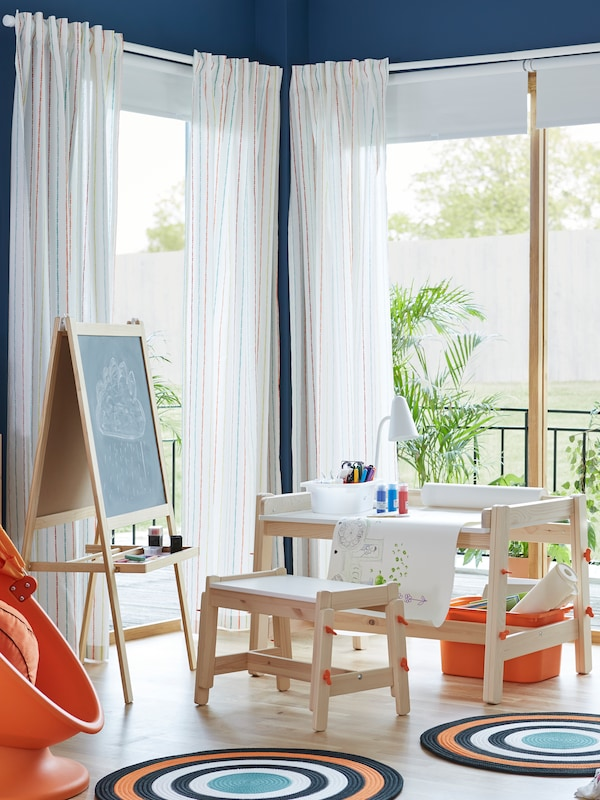 A FLISAT children's bench and a FLISAT children's desk with artists' materials and a lamp on it sit near a balcony door.