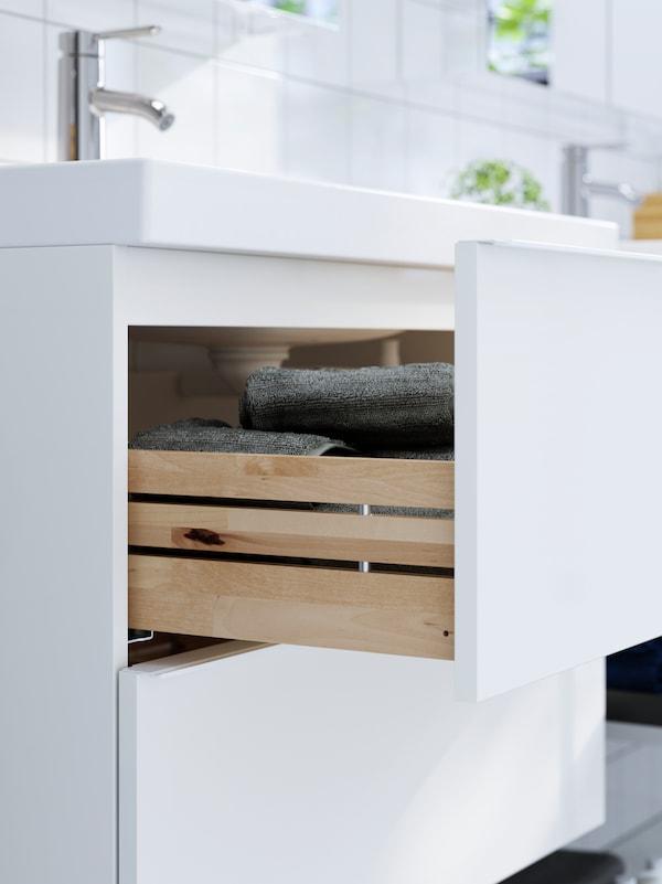 Un set de mască de lavoar de culoare albă cu un sertar deschis, în care se pot vedea prosoape de culoare gri.