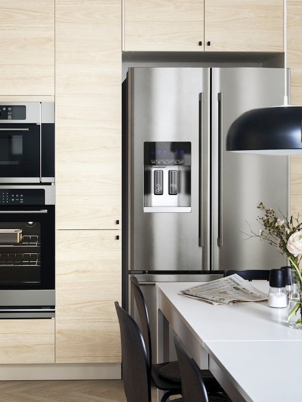 A kitchen with fronts in ash veneer and black knobs with a NUTID French door refrigerator in stainless-steel.