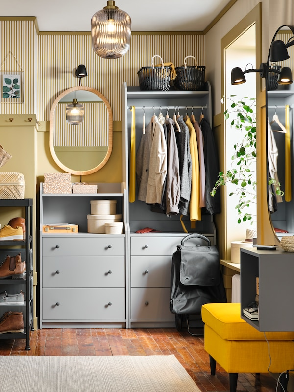 A HAUGA open wardrobe with 3 drawers in grey with clothes on the rail, storage baskets on top, beside an OPPHEM mirror.
