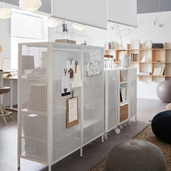 White mesh storage units side by side, with earphones and various clip-boards hanging on them, shelving behind.