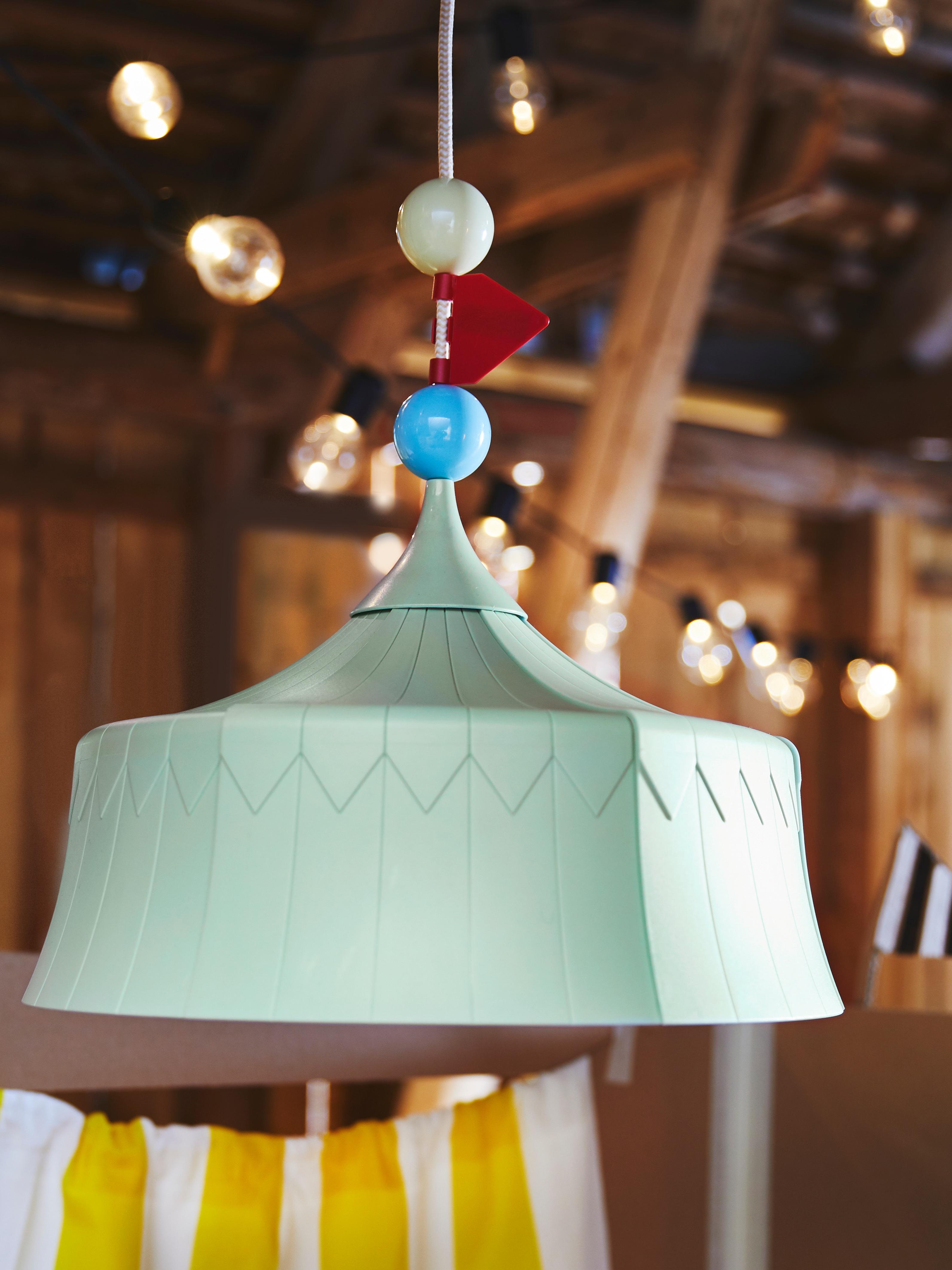 Krupni plan TROLLBO visilice prikazuje svijetlozelenu lampu u obliku cirkuskog šatora i dekoracija na kablu u obliku kugli i zastava.