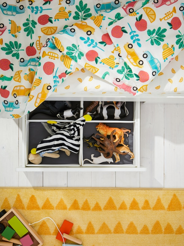 A drawer under a STUVA/FRITIDS cot is pulled out. Inside it are toys organised in RASSLA boxes with compartments.