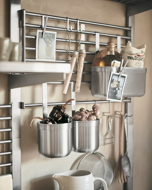 A KUNGSFORS wall grid in stainless-steel with ginger, condiments and cooking utensils displayed in containers and from hooks.
