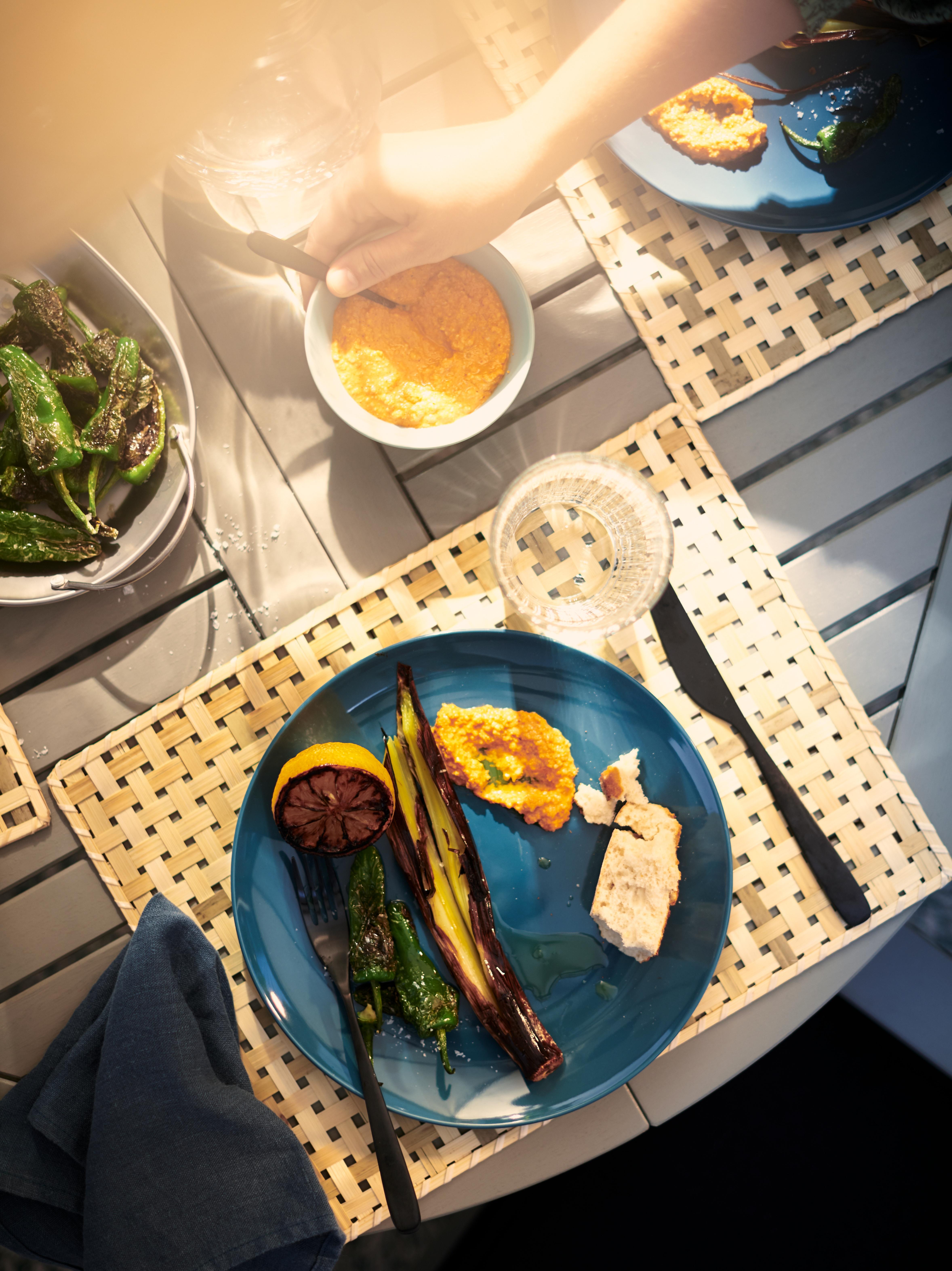 Pogled iz ptičje perspektive na vanjski blagovaonski stol s večerom na plavim FÄRGKLAR tanjurima i podmetačima od prirodnih vlakana.