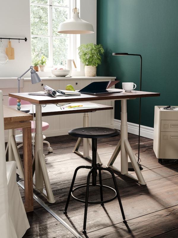 Un bureau avec un ordinateur portable, une tasse, des livres et d'autres objets, une table basse et des sièges à côté, ainsi qu'une suspension blanche et un lampadaire.