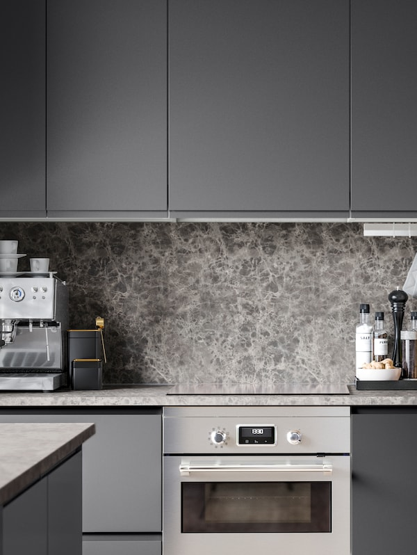 A sleek kitchen with black and white marbled effect splashbacks, grey cabinets and drawers, an oven and espresso maker.