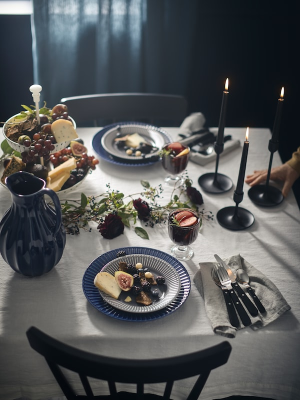 A table with a tablecloth made from DITTE fabric set for two with bowls filled with fruit, candles, and a blue jug on it.