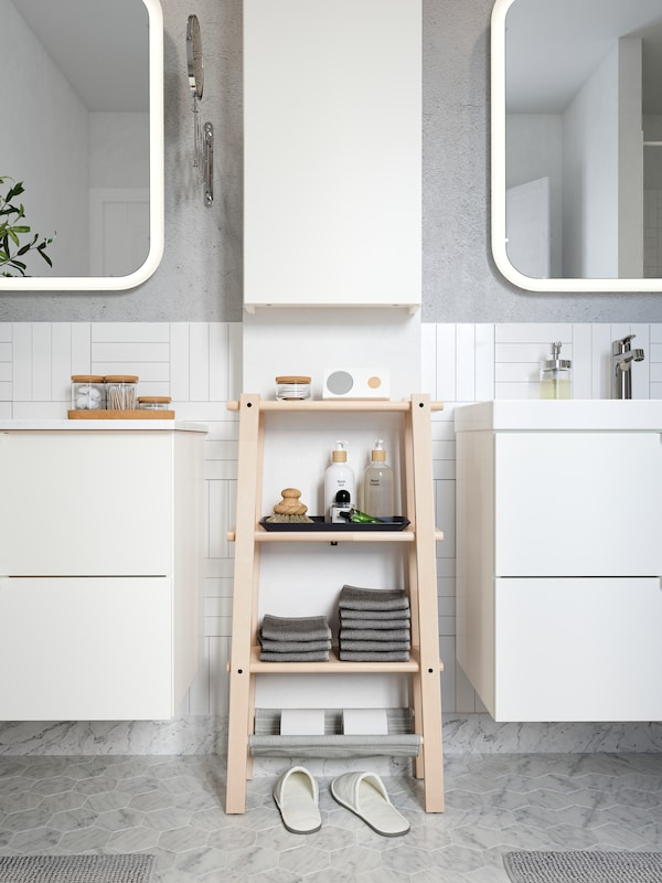 A VILTO shelving unit in birch, placed between two vanity cabinets, stocked with towels, a speaker and beauty products.
