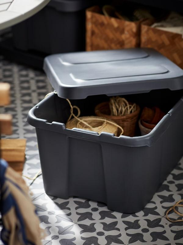 Caixa KLÄMTARE en gris escuro, coa tapa medio aberta e accesorios para sementar no interior, nun chan de azulexos dunha terraza.
