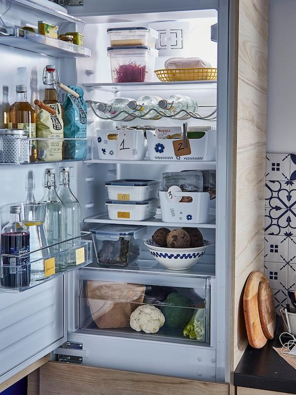 Odprt hladilnik s hrano in pijačo: steklenice v vratih, vsebniki na policah, predal za zelenjavo na dnu.