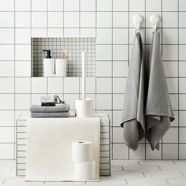 A white tiled bathroom with bathroom accessories and grey towels