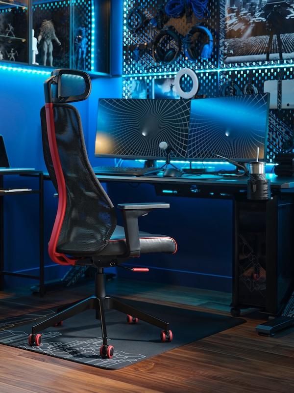 En MATCHSPEL gamingstol framför ett skrivbord med två skärmar. Teknisk utrustning och blå LED-ljuslister hänger på väggen.