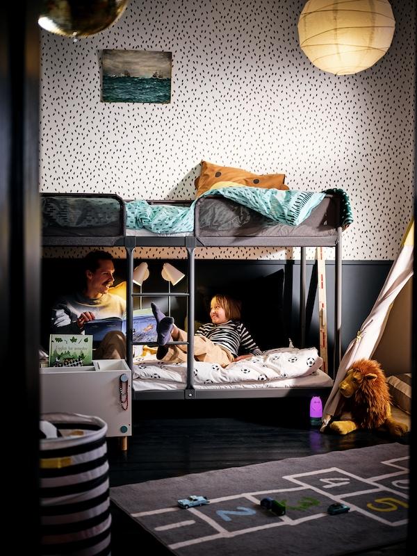 Un père et son fils assis au bas d'un lit superposé dans une chambre d'enfant.