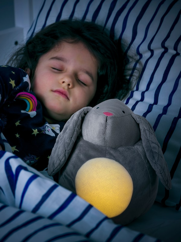 A sleeping child in a bed with striped blue covers snuggles next to a soft toy rabbit with LED night light.