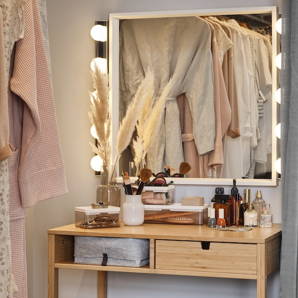 A NORDISKA dressing table with make-up and other items on it and a NISSEDAL mirror on the wall, reflecting a clothes rail.