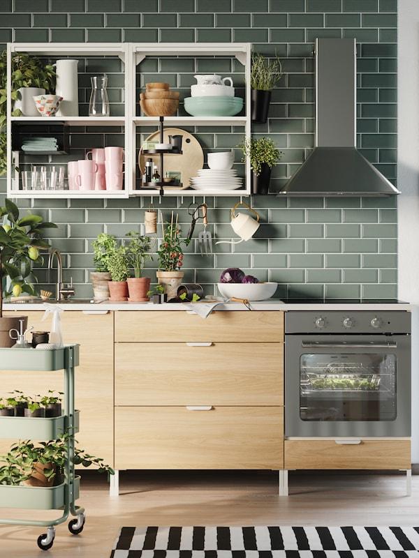 Una cucina con piastrelle verdi, pensili a giorno bianchi, mobili base in legno e un carrello verde con piante.