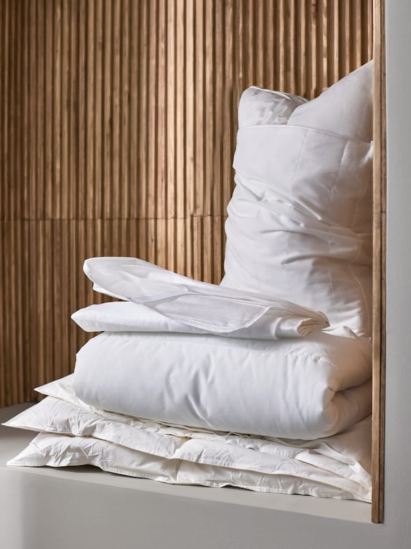 A pile of bedding including a pillow with LUDDROS pillow protector and TAGELSÄV mattress protector against a wooden wall.