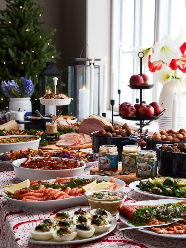 Slavnostně prostřený stůl s tradičním švédským jídlem, jako je losos, vařená vejce, masové kuličky, hořčice, omáčky a další.