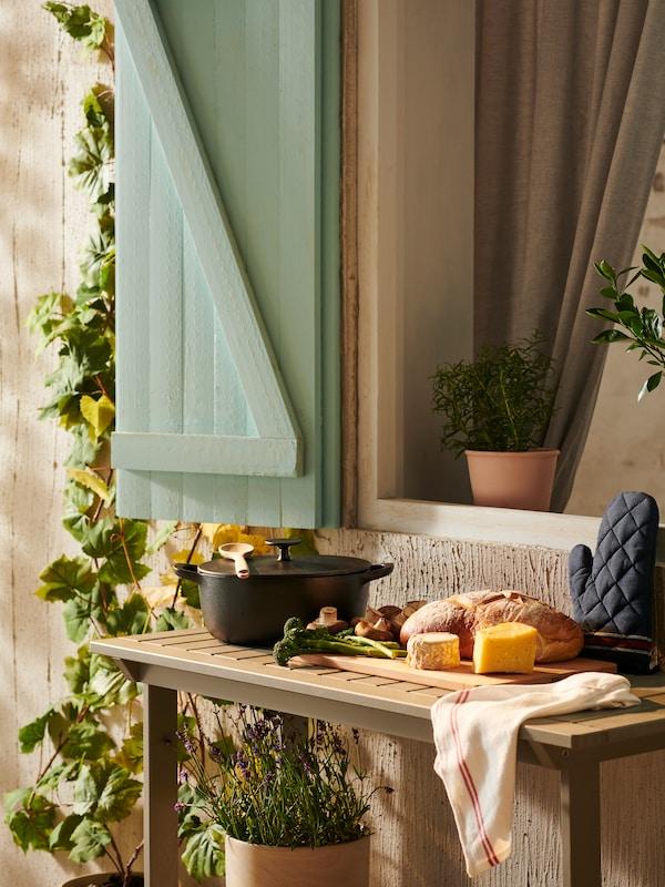 Une table d'appoint placée à l'extérieur, avec une casserole en fonte et une planche à découper remplie de pain et de fromage.