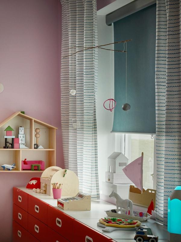 儿童房的窗户上挂着UPPTÅG 乌普托格 窗帘和淡蓝色的TRETUR 加特尔 遮光卷帘,半拉开。
