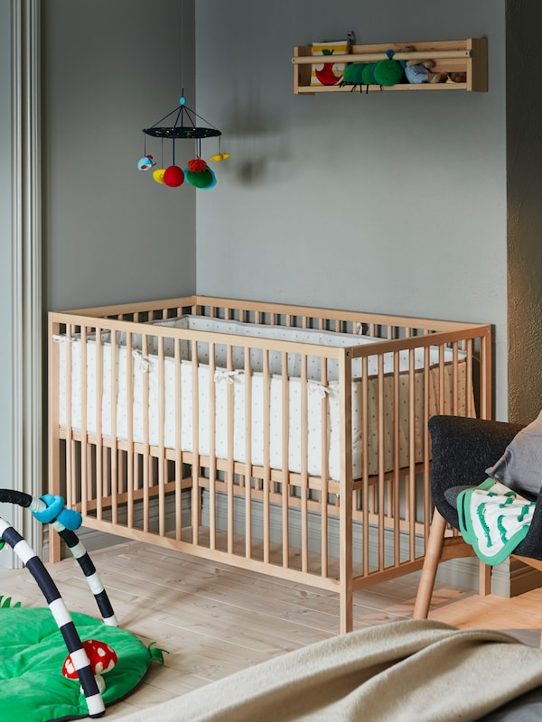 A SNIGLAR cot, with a LENAST bumper pad and a KLAPPA mobile hanging above it, stands in a corner of a children's room.